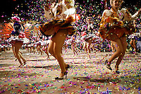Women dance with confetti being thrown at the Carnaval de Oruro. During the fiesta many people sacrifice llamas and give offerings such as coca leaves and cigarettes to show their dedication to the Devil, a Virgin, Pachamama or Mother Earth. The Devil (or Uncle) is a mythical character that protects the miners of Oruro who work in dangerous conditions hundreds of metres below the ground. During the carnival, people dress in outrageous costumes and dance for days before arriving at the Church of Socavon, where they pay their respects to a virgin. Ironically, many of the dancers wear devil costumes.