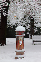 Rome, villa Gordiani: A typical drinking fountain of Rome (in villa Gordiani, on the Prenestina road), with the writing SPQR well readable. There are bare trees and a bench on the background. This is a peculiar view, since it is taken after a snowing night, and the drinking fountain is covered by snow (February 2012).