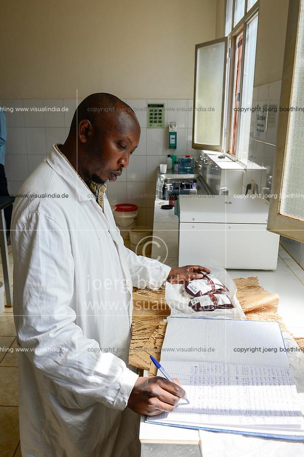 RWANDA, Butare, health center Gikonko, blood preserves delivered by zipline drone / RUANDA, Butare, Institut Saint Boniface, Krankenstation Gikonko, Labor, Mitarbeiter Job packt und registriert Blutkonserven aus, die gerade per zipline Drohne gekommen sind