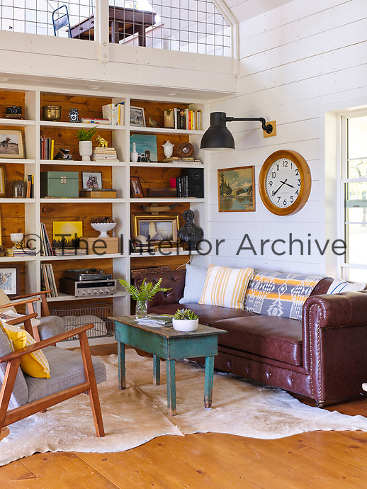 The panelled living room has a cosy corner with a letter sofa and open shelving.