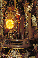 "Incredible complexity of decoration radiant in light from yellow stained-glass window. Statues of Mary, winged angels, cherubs and others in stone or gilt. """"Barley-twist"""" columns. Stone balustrade. Munich Bavaria Germany."