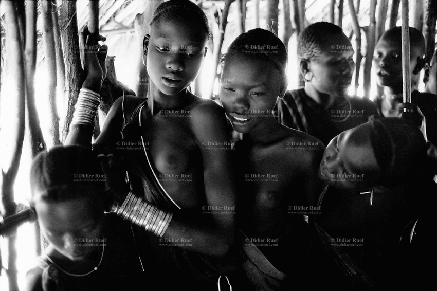 Ethiopia. South Omo Zone. Salamago district. Hana (little village). Bodi tribe. Nomadic. Inside a hut, young girls are waiting for the tetanos vaccination made by the non-governmental organization (NGO) Médecins Sans Frontières (MSF) Switzerland as part of its health project. MSF inoculate children and young girls (future mothers). Bodi women and girls like to have artistic and stylish haircuts. They wear metal bands on their wrist (silver bracelets) and their dresses are made out of cow's leather. The Bodi tribe is located in the Debub Omo Zone (South Omo Zone) of the Southern Nations, Nationalities and Peoples's région. © 2001 Didier Ruef