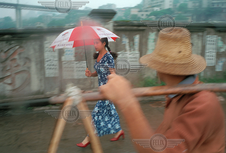 A woman with an umbrella walks along a street alongside the Wanzhou bridge.  The old part of the city has been evacuated to make way for the Three Gorges Dam project.