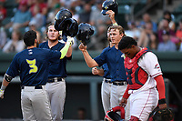 Second baseman Michael Paez (3) of the Columbia Fireflies is greeted by Dash Winningham and Reed Gamache after hitting a home run in a game against the Greenville Drive on Thursday, June 15, 2017, at Fluor Field at the West End in Greenville, South Carolina. Columbia won, 7-2. (Tom Priddy/Four Seam Images)