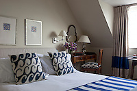 An antique writing desk and chair stands in the corner of a traditional bedroom. The double bed has blue and white pattern cushions