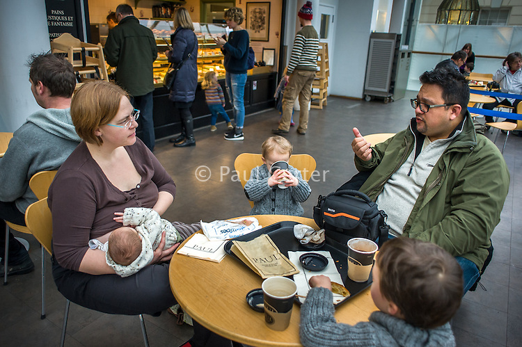A mother with her family breastfeeding her baby while talking to the dad in a museum cafe.<br /> <br /> London, England, UK<br /> 08/03/2015<br /> <br /> © Paul Carter / wdiip.co.uk
