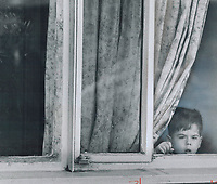 Sad-faced child stares out through broken window in one of 732 housing units in Toronto's run-down Regent Park South housing project.