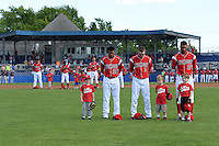 """Batavia Muckdogs players Wildert Pujols (38), Ryan Aper (3) and Kevin Grove (12) stand for the national anthem with young fans as part of the """"Stars of the Game"""" program before a game against the State College Spikes on June 22, 2014 at Dwyer Stadium in Batavia, New York.  State College defeated Batavia 10-3.  (Mike Janes/Four Seam Images)"""