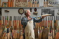 BNPS.co.uk (01202) 558833<br /> Pic: ZacharyCulpin/BNPS<br /> <br /> Tim with the finished product in front of his collection of cricket bats<br /> <br /> Master bat maker Tim Keeley is putting the finishing touches to his beautifully hand-crafted pieces of willow ahead of the forthcoming cricket season.<br /> <br /> Tim, 62, has made almost half a million bats since starting out as an apprentice at Gray Nicholls aged 16 in 1975.<br /> <br /> He is the founder of family business Keeley Cricket, in Battle, East Sussex, which he runs with his brother Nick who has 35 years of bat-making experience.