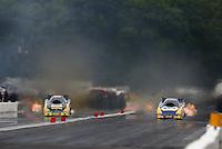 Aug 17, 2014; Brainerd, MN, USA; NHRA funny car driver Jeff Arend (left) races alongside Ron Capps during the Lucas Oil Nationals at Brainerd International Raceway. Mandatory Credit: Mark J. Rebilas-