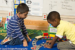 Education Preschool 4 year olds two boys playing together with plastic train set