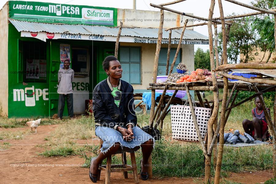 KENIA, County Siaya, village Kotanega, shop M-Pesa, of company Safari.com a joint venture of Vodafone and kenyan telephone, payment by mobile phone, market woman sells vegetables / KENIA, bezahlen per Mobiltelefon, M-Pesa von Safari.com a joint venture von Vodafone and kenyan telephone, Marktfrau verkauft Gemuese