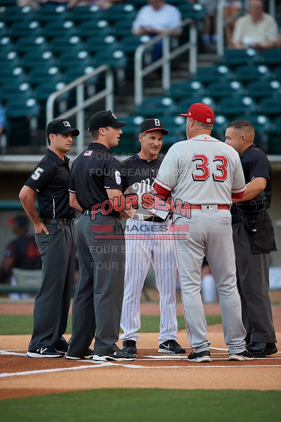 Birmingham Barons manager Omar Vizquel (13) during the lineup exchange with Chattanooga Lookouts manager Pat Kelly (33) and umpires Jonathan Parra (right), Anthony Perez (left), and Matthew Brownduring (center) before a Southern League game on May 2, 2019 at Regions Field in Birmingham, Alabama.  Birmingham defeated Chattanooga 4-2.  (Mike Janes/Four Seam Images)