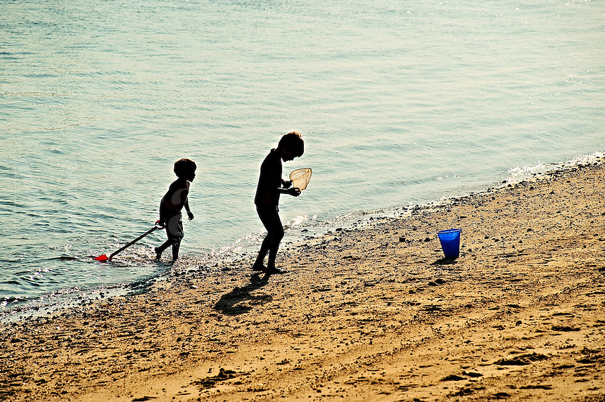 Boy with with fishing net in shallow ocean water, Cape Cod, MA, USA