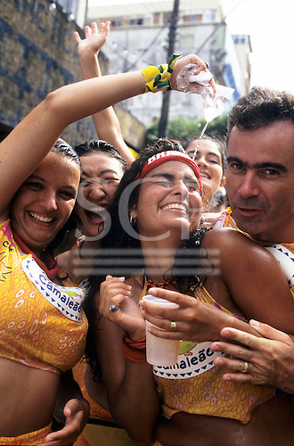 Salvador, Brazil. Carnival revellers cooling off with some cold water and beer; Camaleao.