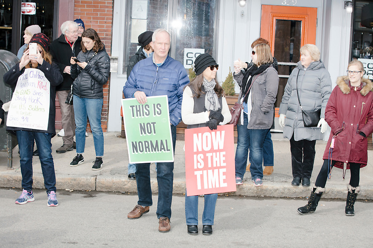 """People take part in the March For Our Lives protest, walking from Roxbury Crossing to Boston Common, in Boston, Massachusetts, USA, on Sat., March 24, 2018, in response to recent school gun violence. Here people hold signs reading """"This is not normal"""" and """"Now is the time."""""""
