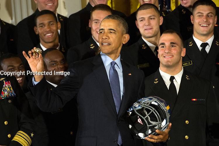 President Barack Obama holds a U.S. Naval Academy football helmet while inspecting a team ring presented to him after he awarded the Commander in Chief's Trophy to the team at the White House in Washington, D.C. April 27, 2016. The president presents the trophy to Department of Defense academy team with the most victories against its service rivals. (DoD News photo by EJ Hersom)