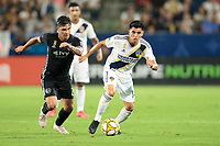 CARSON, CA - SEPTEMBER 15: Joe Corona #14 of the Los Angeles Galaxy and Felipe Gutierrez #19 of Sporting Kansas City battle for a loose ball during a game between Sporting Kansas City and Los Angeles Galaxy at Dignity Health Sports Complex on September 15, 2019 in Carson, California.