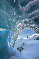 Man on cross country skis peers into the entrance of a glacier ice cave in the Alaska Range mountains, Interior, Alaska.