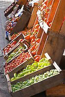 A fruit and vegetable shop displaying products in wooden crates on the street: tomatoes, Brussels sprouts, oranges, peppers Montevideo, Uruguay, South America