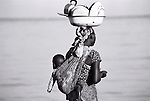 A woman carries her dishes to wash them on the shores of  Lake Malawi. The lake is the third largest lake in Africa, and measures 550 kilometres long, and spreads into Tanzania and Mozambique.