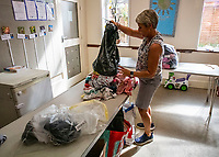 BNPS.co.uk (01202 558833)<br /> Pic: MaxWillcock/BNPS<br /> <br /> Pictured: A volunteer sorting donations for babies.<br /> <br /> A flood of donations for Afghan refugees has inundated a church which has been left with a 24ft long stack of parcels.<br /> <br /> Ross Donaldson posted on a Facebook community group asking if anyone had clothes to offer, sparking an overwhelming response from his community.<br /> <br /> After organising to keep donations at Immanuel Church, Bournemouth, Dorset, he arrived the next morning to find a pile of bags.