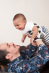 6 month old baby boy held aloft by father interaction