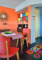 The orange-painted dining area features simple red chairs and a brightly patterned rug