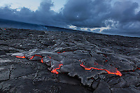 Molten lava glowing at dusk in Hawai'i Volcanoes National Park, Hawai'i Island.
