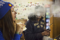 USA. Colorado state. Denver. Dabbing in iBAKE Denver, the first private membership head-shop that people can smoke marijuana in. Anna (L) and her boyfriend Hollywood (R) are dabbing which is a slang term used to describe taking single dose hash hits of concentrates that are referred to as oil, erl, earwax, wax, budder, BHO or shatter using pipes and bongs that are made specifically for smoking these cannabis extracts. The pieces are designed to have a skillet or nail that made from glass, quartz or titanium that is heated with a handheld torch, the user then 'dabs' a small of the extract onto the hot nail causing the concentrate to flash into a vapor that you inhale. Dabbing is the street name for use concentrated butane hash oil, which has THC concentrations as high as 75% (allegedly reaching the 90+ range in some cases) compared with typical pot concentration of about 10 to 15 percent. Depending on the concentrate one long, hard hit can feel as having five blunts at once. The result is a rapid and very strong high. Cannabis, commonly known as marijuana, is a preparation of the Cannabis plant intended for use as a psychoactive drug and as medicine. Pharmacologically, the principal psychoactive constituent of cannabis is tetrahydrocannabinol (THC); it is one of 483 known compounds in the plant, including at least 84 other cannabinoids, such as cannabidiol (CBD), cannabinol (CBN), tetrahydrocannabivarin (THCV), and cannabigerol (CBG). 18.12.2014 © 2014 Didier Ruef