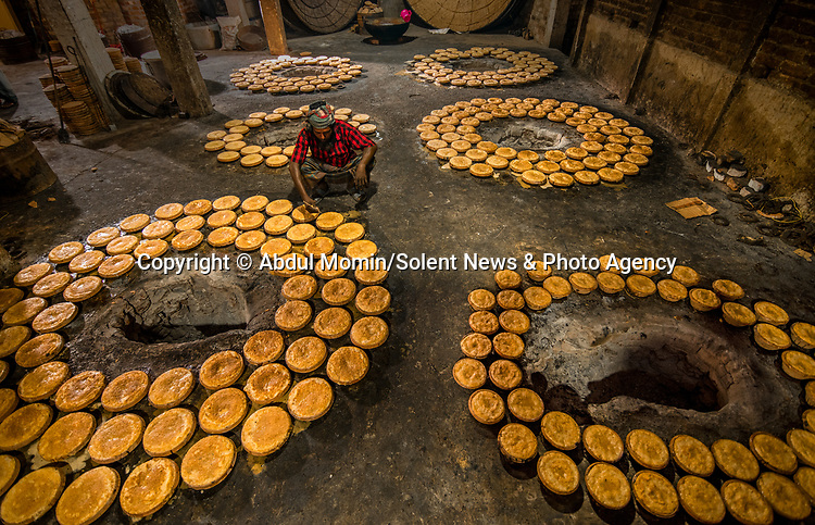 "Hundreds of clay pots are filled with curd as workers make the traditional dish in a Bangladeshi factory.  Photos taken in the country's largest curd making plant illustrate the process which sees 3,000 pots delivered in a day.<br /> <br /> The sweet dish, which is made by boiling milk to reduce it and mixing in yoghurt and sugar, is called 'Mishti Doi'.  Photographer Abdul Momin, who visited the factory in Sherpur Upazila to take these pictures, said: ""It is made by boiling the milk until it's reduced to half and thickened.  SEE OUR COPY FOR DETAILS.<br /> <br /> Please byline: Abdul Momin/Solent News<br /> <br /> © Abdul Momin/Solent News & Photo Agency<br /> UK +44 (0) 2380 458800"