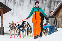 Musher and checkpoint helper Meredith Mapes leads Jason Campeau's team down the hill in preparation to leave from his mandatory 24-hour layover in the morning at the Takotna checkpoint during the 2019 Iditarod on Thursday, March 7th 2019.<br /> <br /> Photo by Jeff Schultz/  (C) 2019  ALL RIGHTS RESERVED