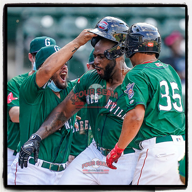 First baseman Tyreque Reed (38) of the Greenville Drive is greeted at home plate after hitting a walk-off home run in a 10-9 win over the Brooklyn Cyclones on Sunday, May 16, 2021, at Fluor Field at the West End in Greenville, South Carolina. (Tom Priddy/Four Seam Images)