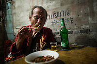 """An elderly man who asked not to be named eats fried noodles with peanuts and spices at a small unnamed outdoor noodle cafe at the bottom of Shibati, or 18 Steps, in central Chongqing. He called the dish dou gan. The man says he eats at the restaurant almost every night because he likes the flavors of the dishes so much.<br /> <br /> The cook, Tong Su Chun, has been cooking at the spot, which is run by his nephew, for about 20 years. The neighborhood is slated for redevelopment, and all residents, including this shop, must leave the area by October 2014. Tong Su Chun said he didn't know what he would do after the restaurant closes. """"I'll take a break,"""" he said, """"and then find something new."""" The restaurant typically serves a couple hundred people in a night, most spending about 15 RMB."""
