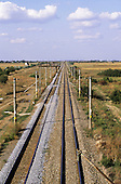 Bucharest, Romania. Electrified railway line with fresh laid ballast stretching into the distance