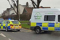 """COPY BY TOM BEDFORD<br /> Pictured: A police car pulls out a speed camera van that got stuck on a grass verge in the village of Laleston, Bridgend, Wales, UK.<br /> Re: A speed camera van that got itself firmly wedged on top of a roadside verge had to be towed free by police – much to the amusement of a passing motorist.<br /> The comical scene was captured on camera by a driver from Bridgend.<br /> He was passing through the village of Laleston, Bridgend when he saw the Ford Transit, in the livery of the GoSafe partnership, in a bit of a pickle.<br /> """"I think they must have tried to get onto the old concrete slab which I think was an old bus stop,"""" said the man, who did not wish to be named.<br /> """"But I think he tried to go over the high curb and got stuck."""""""
