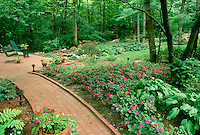 Brick path to secluded patio in back yard with two chairs looking over blooming gardens