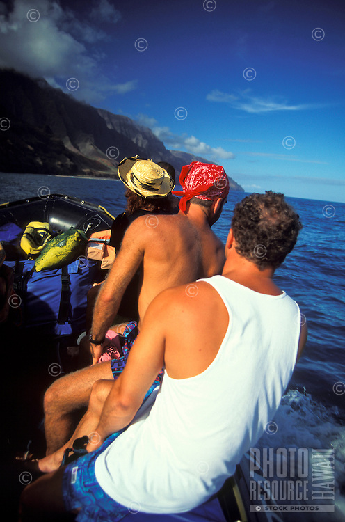 People riding a in a zodiac inflatable along Kauai's Na Pali northern coastline