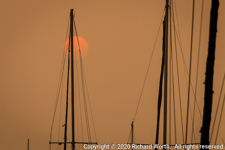 An orange disk in an orange sky, the smoke filtered sun and sail boat masts and rigging at a marina along San Francisco Bay, September 13, 2020.