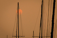 An orange disk in an orange sky, the smoke filtered sun and sail boat masts and rigging at a marina along San Francisco Bay, September 13, 2020.