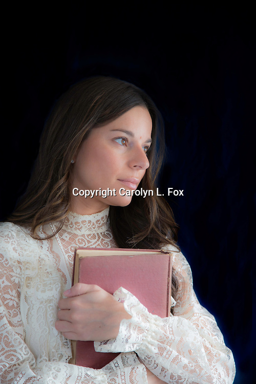 A young woman wearing a pretty dress hugs an old, antique book.