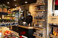 fruttivendolo con maschera di protezione, alla cassa. vegetable shop owner  with protective mask