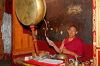 Buddhist monk beats ceremonial drum, or rnga, with sickle-shaped drumstick, clashes cymbals, or rol mo, on lap and chants mantra at Sera Monastery, Lhasa, Tibet, China.