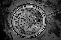 Street water meter cover in black & white. New Orleans Louisiana United States French Quarter.
