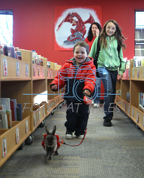 Cash Marin, 3, and Xena Allen, 12, play with Morpheus during a Love on A Leash event at the Carson City Library, in Carson City, Nev., on Saturday, Dec. 17, 2011. .Photo by Cathleen Allison