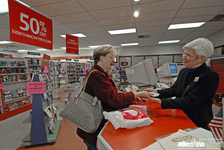 B. Dalton bookstore manager Nancy Kenish, right, accepts a customer's payment for the last book to be sold at the B. Dalton store at a Westerville, Ohio, suburban strip center. The store, one of the smallest in the chain, was closing after nearly two decades tucked in the corner of a building housing an insurance company and a balloon store.(Gary Gardiner/EyePush Newsphotos)<br />