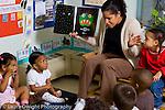Preschool Headstart female teacher reading to group of 3 year olds horizontal