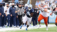 CHAPEL HILL, NC - OCTOBER 10: Javonte Williams #25 of North Carolina is chased by Jermaine Waller #28 and Jarrod Hewitt #5 of Virginia Tech on a 29-yard run during a game between Virginia Tech and North Carolina at Kenan Memorial Stadium on October 10, 2020 in Chapel Hill, North Carolina.