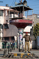 India, Dehradun.  Policeman at Traffic Intersection using his Cell Phone.