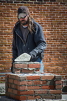 Brick mason lays another layer of mortar as he builds a signpost at the entrance to city hall in Westerville.